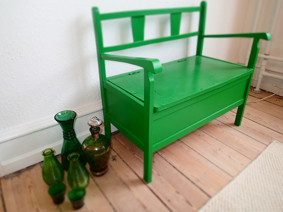 木目の床の上に緑色の小さな椅子とガラスの瓶が置いてある