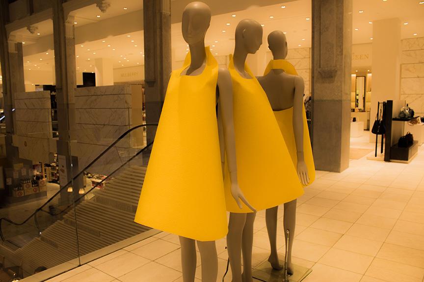 黄色のワンピースを着たマネキン3体がデパートのエスカレーター近くに立っている